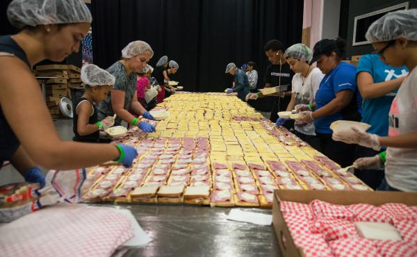 """Volunteers assemble tens of thousands of sandwiches each day at the Coliseo in San Juan, Puerto Rico. Chef José Andrés, who is overseeing the massive effort to feed displaced Puerto Ricans, calls it """"one of the most effective sandwich lines made by volu"""