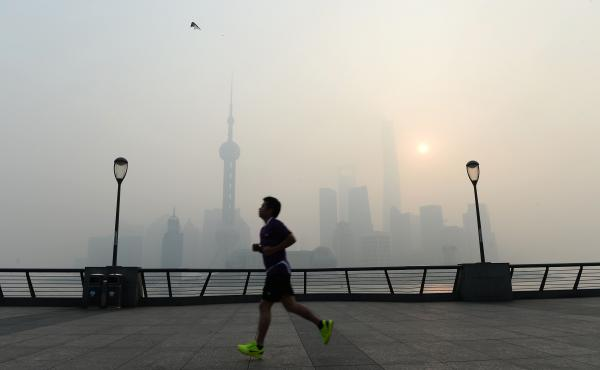 A jogger goes for a run amid heavy smog in Shanghai on Wednesday. China has for the first time agreed to limit its carbon emissions, but critics are questioning whether the move goes far enough.