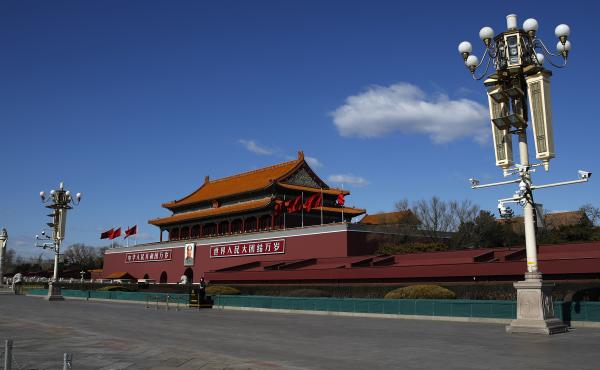 A masked paramilitary policeman stands guard alone at a deserted Tiananmen Gate in Beijing following the coronavirus outbreak. China on Wednesday said it has revoked the press credentials of three U.S. reporters over a headline for an opinion column it de