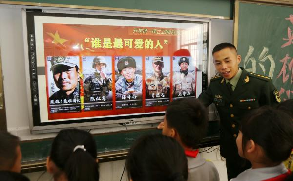 A paramilitary police officer talks next to a screen showing frontier soldiers of the People's Liberation Army during an event at a primary school in Wuzhishan, Hainan province, China, on Feb. 22. On the screen are (L-R) Qi Fabao, who was seriously wounde