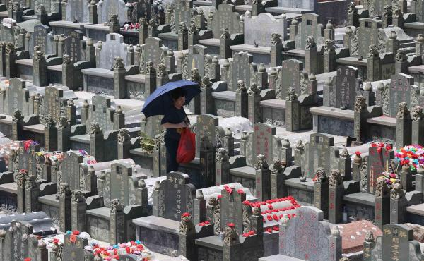 A mourner walks through a cemetery in Jinjiang during the Tomb-Sweeping Festival in 2015.