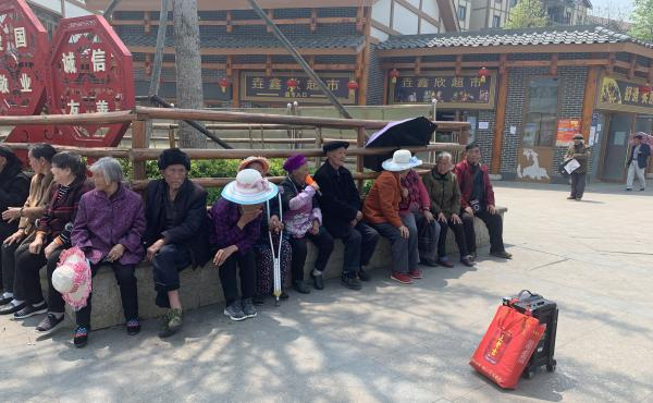 Resettled villagers sun themselves outside Qixingguan. Many older residents have had a difficult time adjusting to life away from their fields.