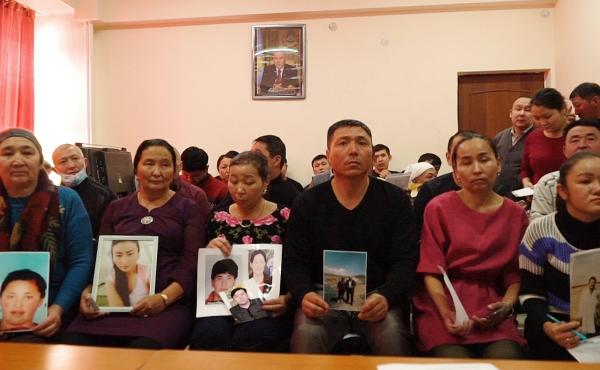 Relatives of people missing in China's western region of Xinjiang hold up photos of their family members at an office of a Chinese Kazakh advocacy organization in Almaty, Kazakhstan.
