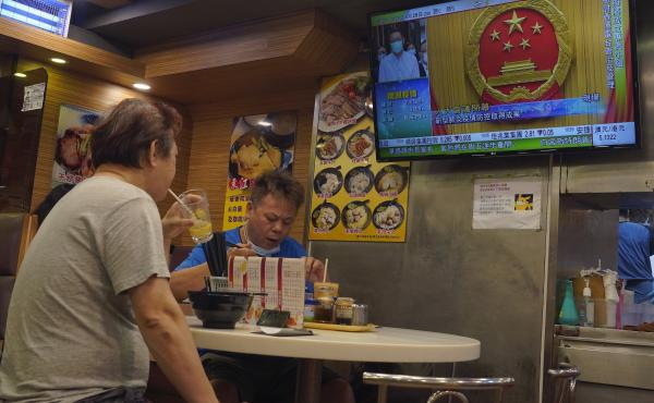 The closing session of China's National People's Congress plays on a television in a Hong Kong restaurant Thursday.