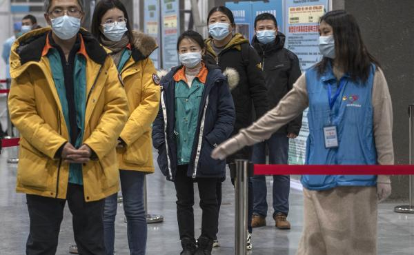 Chinese workers wait to receive a COVID-19 vaccine jab at a mass vaccination center in Beijing on Jan. 5. Even with at least 5 homegrown vaccines nearing approval, China is setting a modest initial goal: 50 million people vaccinated by mid-February — ab