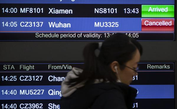 A traveler walks past a display board showing a canceled flight from Wuhan at Beijing Capital International Airport on Thursday. China closed off the city of more than 11 million in an unprecedented effort to try to contain a deadly new viral illness that