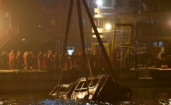 People watch the bus wreck being raised out of water in Wanzhou in southwest China's Chongqing Municipality early Thursday.