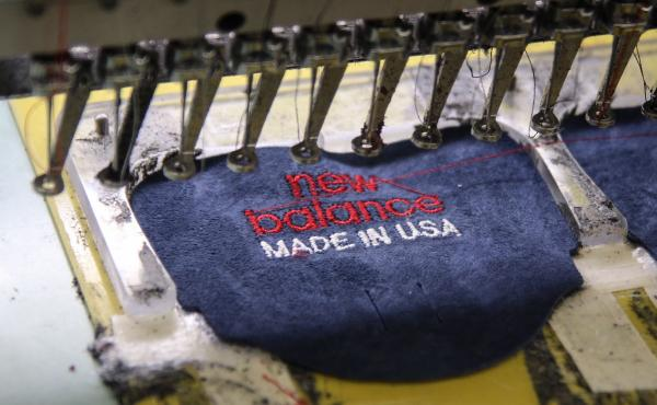 Automated sewing machines embroider oversized patches for the tongues of New Balance sneakers at a factory in Skowhegan, Maine.
