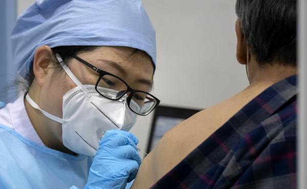 A medical worker gives a coronavirus vaccine shot to a patient at a vaccination facility in Beijing, in January. Two pharmaceutical companies in China announced Wednesday they are seeking market approval for new vaccines.