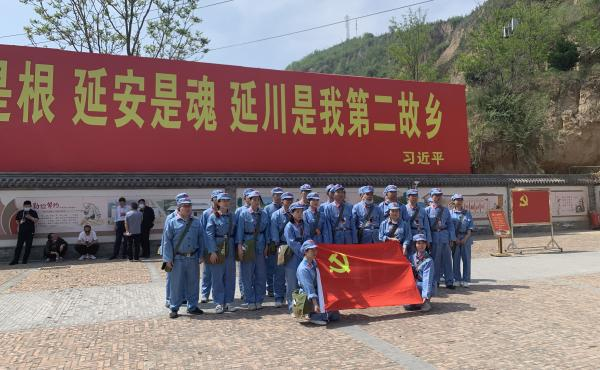 """Tourists dressed up as People's Liberation Army soldiers pose in Liangjiahe village, where a teenage Xi Jinping spent seven years doing hard labor. Today the village is a popular red tourism site. The sign displays a quote from Xi: """"Liangjiahe is where my"""