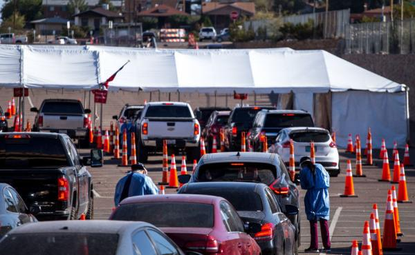 Medical workers wearing personal protective equipment register people in vehicles at a drive-through coronavirus testing site Monday in El Paso, Texas.