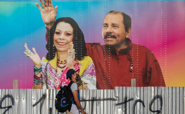 A man walks by a mobile health clinic displaying a picture of Nicaraguan President Daniel Ortega (right) and his wife and vice president, Rosario Murillo, in Managua on April 14, 2020. The government claims to be successfully combating the pandemic but he