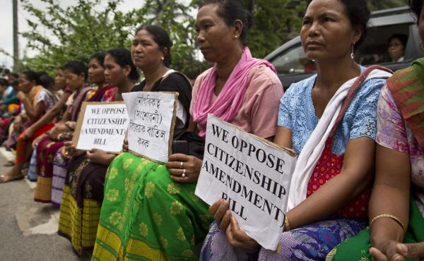 Indigenous women in traditional attire hold placards to protest against the Indian government decision to provide citizenship or stay rights to minorities from Bangladesh, Pakistan and Afghanistan in India in Gauhati, India, in a protest held in May.