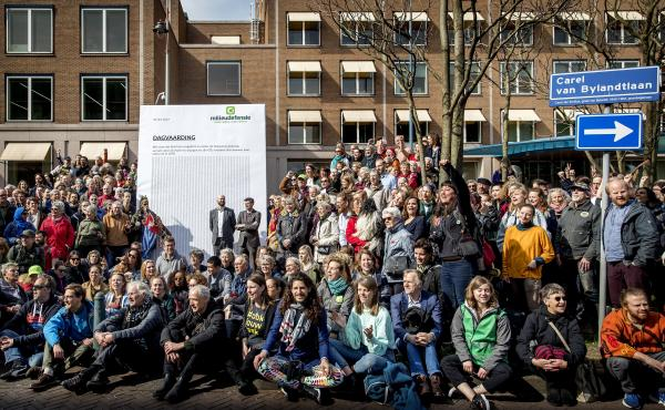 Activists march to Shell's headquarters in The Hague, Netherlands, in April 2019, delivering a legal summons to the company. The civil case began Tuesday, with plaintiffs demanding the company reduce its carbon dioxide emissions.