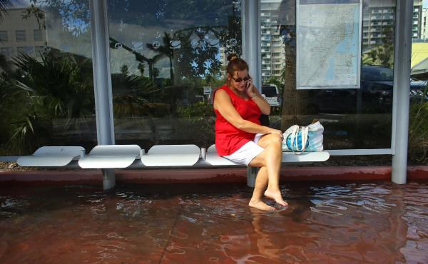Cindy Minnix waits for a bus in a flooded street on Oct. 18, 2012, in Miami Beach. A changing climate is making floods related to high tides more frequent, scientists say.