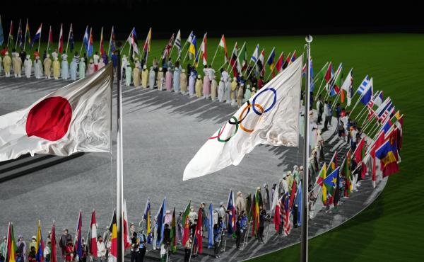 The Japan and Olympic flags fly as country flags are carried in during the closing ceremony in the Olympic Stadium at the Summer Olympics on Sunday in Tokyo.