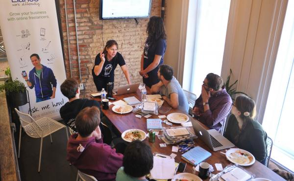People gather around a speaker during a lunchtime seminar at a WeWork co-working space in Washington, D.C.
