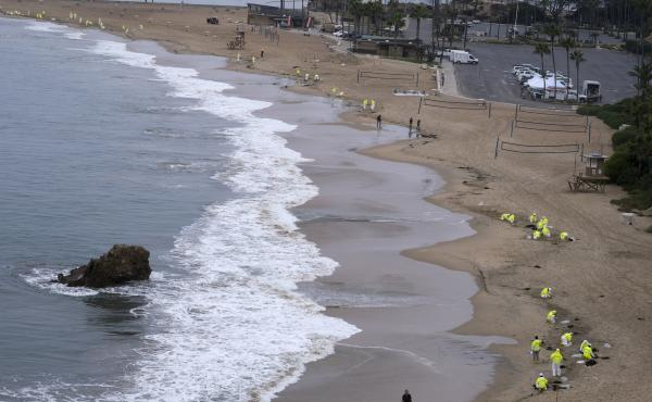 Workers in protective suits clean the contaminated beach in Corona Del Mar on Oct. 7 after an oil spill in Newport Beach, Calif.