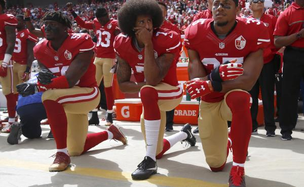 From left, Eli Harold (58),  Colin Kaepernick (7) and Eric Reid (35) kneel during the national anthem before their NFL game against the Dallas Cowboys on Sunday, Oct. 2, 2016.