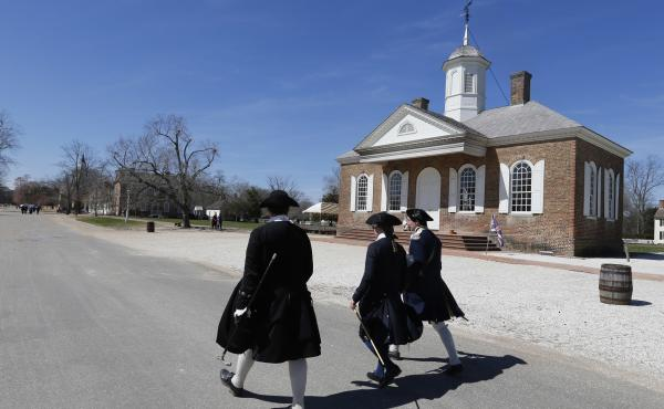Colonial actor-interpreters walk in front of the courthouse on Duke of Gloucester Street in Colonial Williamsburg in Virginia in 2015.