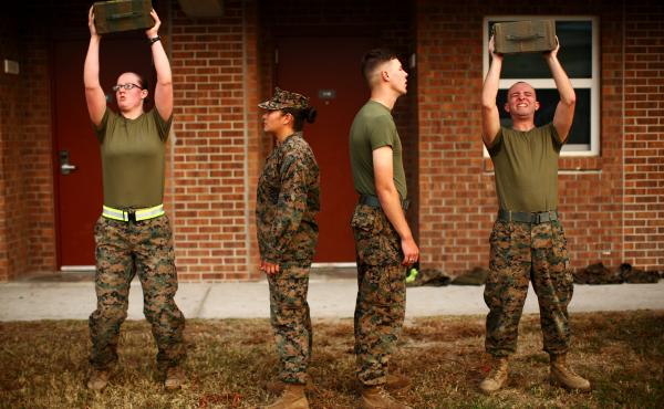 Katie Gorz (left) performs the ammo can lift next to male Marines as they go through the combat fitness test. The Marine Corps is experimenting with inserting some women into combat infantry roles that have historically been limited to men. At Camp Lejeun