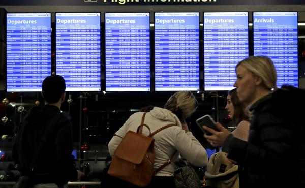 Travelers walk and check their flight information in Terminal 3 at Chicago's O'Hare International Airport in December.