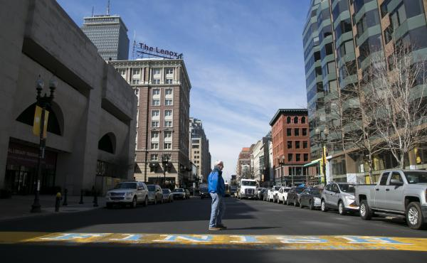 A pedestrian walks along the finish line of the Boston Marathon on Boylston Street in April 2014. Of the 160 companies near the explosions that submitted claims for property damage or business losses, nearly 14 percent had coverage for terrorism.