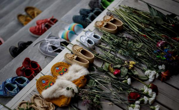 Flowers, shoes and moccasins sit on the steps of the main entrance of the former Mohawk Institute, which was a residential school for Indigenous kids, in Brantford, Ontario. The memorial is to honor the children whose remains were discovered in unmarked g