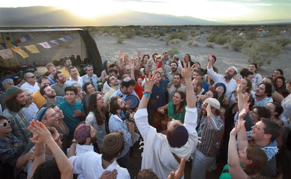 Wilderness Torah festival attendees take their Shabbat celebration outside the Tent of Meeting (at left) as the sun sets in the Panamint Valley of the Mojave Desert in 2014. At center in white, with both arms reaching up to the sky, is singer-songwriter M