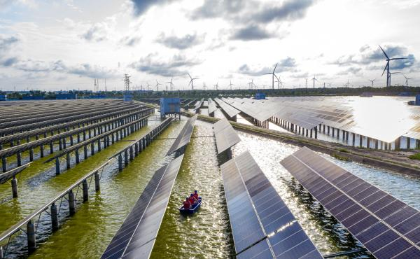 Electrical workers check solar panels at a photovoltaic power station built in a fishpond in Haian in China's eastern Jiangsu province.