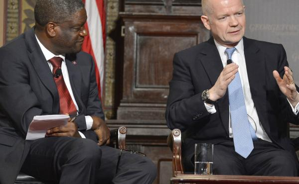 Dr. Denis Mukwege (left) listens as Britain's Foreign Secretary William Hague speaks after the two men were presented Georgetown University's annual Hillary Rodham Clinton Award for Advancing Women in Peace and Security, at Georgetown University in Washin