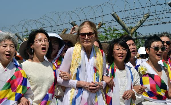 Gloria Steinem and South Korean peace activists march along a military fence at a checkpoint after crossing the border separating North and South Korea.