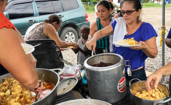 A team of volunteers cooks for African migrants living at a camp in their town of Paso Canoas, Costa Rica.