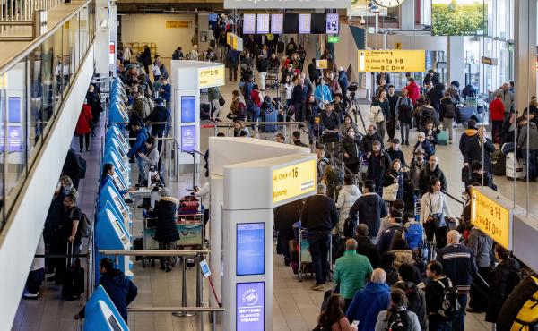 Passengers hoping to change their flights to the U.S. wait in long lines at Amsterdam Airport Schiphol in the Netherlands after President Trump announced new restrictions on travel from Europe.