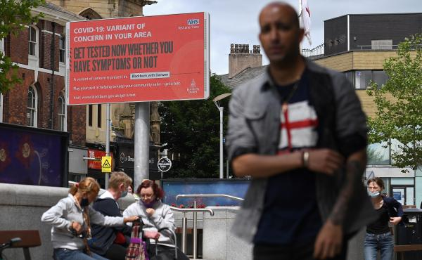 A sign urges people to get tested for a COVID-19 variant in Blackburn, England. The U.K. is experiencing a surge in the delta variant, which was first identified in India.
