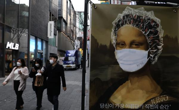 South Korea's KF94 mask does a good job concealing the Mona Lisa's smile — but how effective is it at preventing coronavirus spread? Here, masked pedestrians stroll through a shopping district in Seoul.