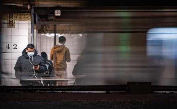 A commuter wearing a medical mask waits for a train Thursday at Grand Central station in New York City. Several dozen cases have been confirmed in the state, and the East Coast as a whole saw its first two confirmed deaths related to COVID-19, in Florida.