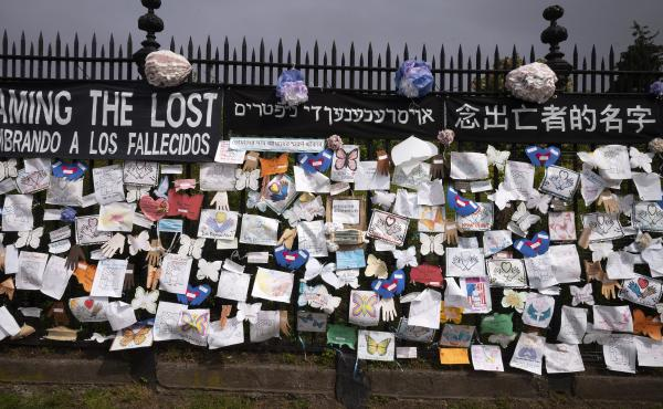 A fence outside Brooklyn's Green-Wood Cemetery is adorned with tributes to victims of COVID-19 on Thursday in New York.
