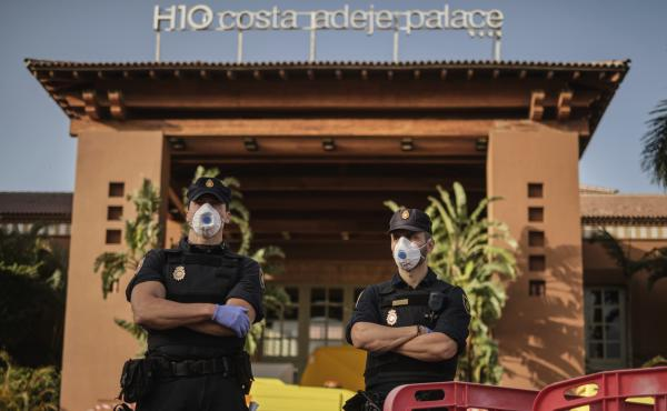 Police officers wear face masks Wednesday in front of a hotel on Tenerife, the largest of Spain's Canary Islands. Spanish officials say a hotel on the island has been placed under quarantine after an Italian doctor staying there tested positive for the ne