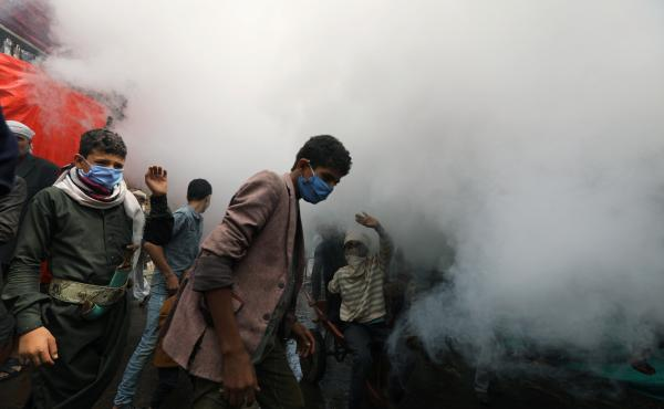 People wear face masks in Sanaa, Yemen, as health workers fumigate a market over concerns about the spread of COVID-19.