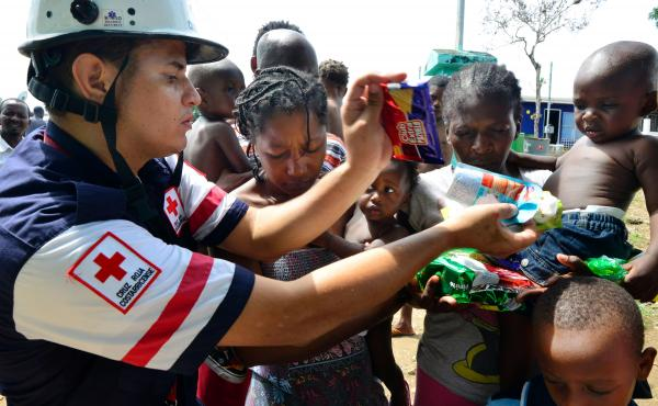 A Costa Rican Red Cross member distributes food to migrants in an encampment of Africans in Penas Blancas, Guanacaste, Costa Rica, on July 19. In a makeshift camp hundreds of tents shelter Haitians, Congolese, Senegalese and Ghanaian migrants waiting to c