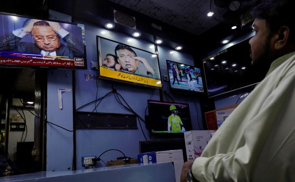 A Pakistani court sentenced former military ruler Pervez Musharraf to death Tuesday, on charges of high treason and subverting the constitution. Here, a shopkeeper watches TV coverage of the news at a shop in Karachi.