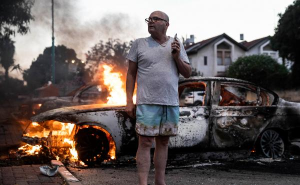 Jacob Simona stands by his burning car during clashes with Israeli Arabs and police in the mixed Jewish-Palestinian city of Lod, Israel, on Tuesday.