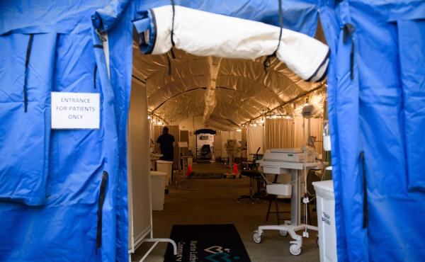 A field hospital tent for suspected COVID-19 patient triage was set up outside the emergency department of Martin Luther King Jr. Community Hospital in Los Angeles, California. A surge in deaths has prompted the county to lift environmental limits on the