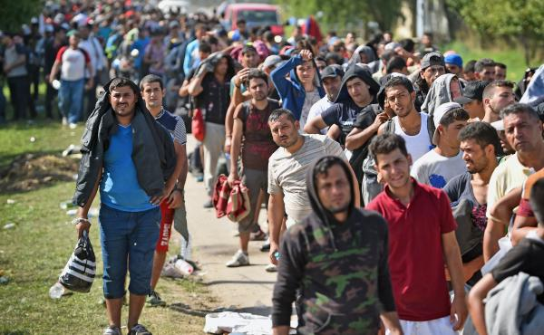 Refugees and other migrants wait to board buses at Tovarnik railway station in Croatia after crossing from Serbia on Friday. Officials say they were forced to close eight road border crossings Thursday after thousands of people entered the country when Hu