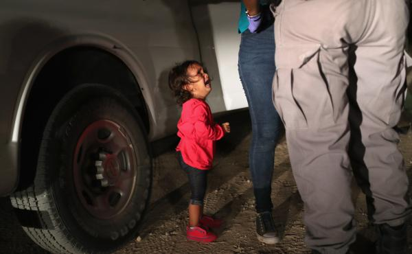 A 2-year-old Honduran girl cries as an official searches her mother in McAllen, Texas, near the U.S.-Mexico border, earlier this month. For many, the image has become indelibly associated with a Trump administration policy that for weeks separated migrant