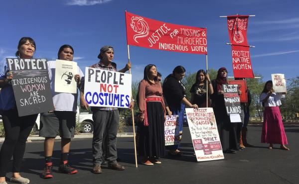 "Native American protesters stand outside the Phoenix office of Yandy.com, a retailer of ""sexy Native American"" costumes on Oct. 24, 2018. For some ethnic and racial groups, Halloween has long been haunted by costumes that perpetuate stereotypes and instan"