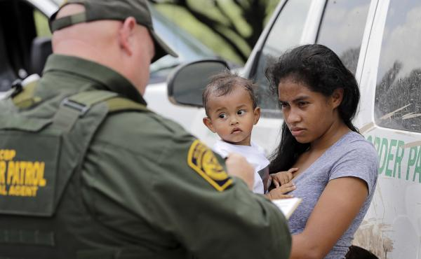 President Trump's zero tolerance policy left the CBP struggling to process the number of people it detained — and the agency says it will temporarily stop turning immigrant parents over to prosecutors. Here, a mother migrating from Honduras holds her 1-