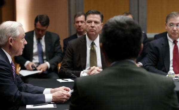 U.S. Attorney General Jeff Sessions (left) speaks with former FBI Director James Comey (center) and other officials at the Department of Justice in April 2017, in Washington.