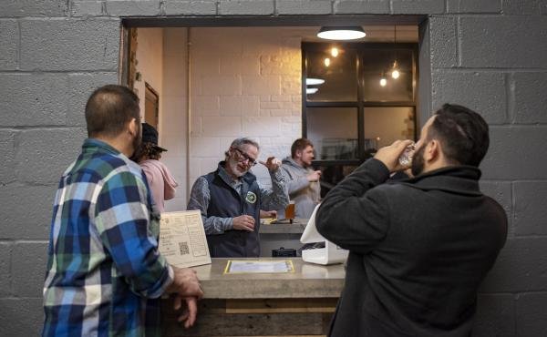 """Co-founder Mark Burke signs with patrons at Streetcar 82 Brewing Co., in Hyattsville, Md. """"My goal is to make the best beer,"""" Burke said. """"But the impact and magnitude of how this influences the Deaf community is inspiring."""""""